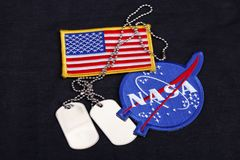 15 March 2018 - The National Aeronautics and Space Administration (NASA) emblem patch, dog tags, and US Flag patch on black. Uniform background stock image
