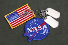 15 March 2018 - The National Aeronautics and Space Administration (NASA) emblem patch, dog tags, and US Flag patch on green. Uniform background royalty free stock image
