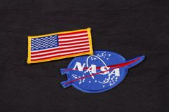15 March 2018 - The National Aeronautics and Space Administration (NASA) emblem patch and US Flag patch on black uniform. Background stock images