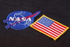 15 March 2018 - The National Aeronautics and Space Administration (NASA) emblem patch and US Flag patch on black uniform. Background royalty free stock images