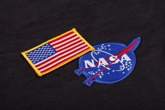 15 March 2018 - The National Aeronautics and Space Administration (NASA) emblem patch and US Flag patch on black uniform. Background royalty free stock photos