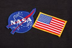 15 March 2018 - The National Aeronautics and Space Administration (NASA) emblem patch and US Flag patch on black uniform. Background stock photos
