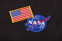 15 March 2018 - The National Aeronautics and Space Administration (NASA) emblem patch and US Flag patch on black uniform. Background royalty free stock photo