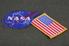 15 March 2018 - The National Aeronautics and Space Administration (NASA) emblem patch and US Flag patch on green uniform. Background stock photo