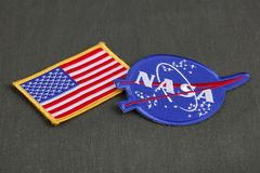 15 March 2018 - The National Aeronautics and Space Administration (NASA) emblem patch and US Flag patch on green uniform. Background stock photos