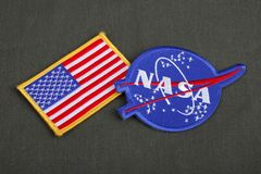 15 March 2018 - The National Aeronautics and Space Administration (NASA) emblem patch and US Flag patch on green uniform. Background stock photography