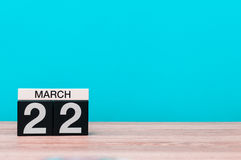 March 22nd. Day 22 of month, calendar on table with turquoise background. Spring time, empty space for text Stock Photography