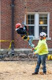 Child and worker laugh as a little girl is lifted into the air. March 17, 2019 New Carlisle Indiana USA ; a child laughs as a tree worker helps lift her into the royalty free stock photography