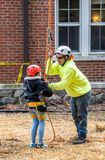 Tree worker puts a harness on a little girl at an event. March 17, 2019 New Carlisle Indiana USA; a worker at the st joseph parks sugar camp days event, prepares royalty free stock photos