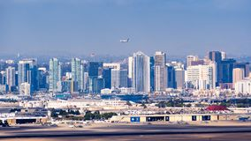 March 19, 2019 San Diego / CA / USA - Panoramic view of the downtown skyline; San Diego Naval Base on Coronado Island visible in. The foreground; Fedex airplane stock image