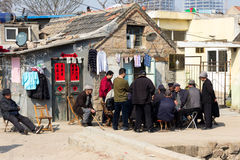 March 2014 - Shandongtou, Qingdao, China. March 2014 - Qingdao, China - A group of men playing cards in the poor neighborhood of Shandongtou Stock Photography