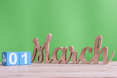 March 1st. Day 1 of month, daily wooden calendar on table and green background. Spring time, empty space for text Stock Photos