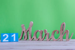 March 21st. Day 21 of month, daily wooden calendar on table and green background. Spring time, empty space for text Stock Image