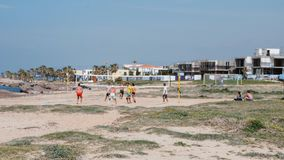 March 21st, Paphos, Cyprus Group of attractive caucasian young guys with trained bodies playing volleyball on beach. Tanned hot me