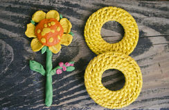 8 March symbol and handmade plasticine flower on wooden background. Happy woman`s day design. Can be used as a decorative greeting Stock Photos