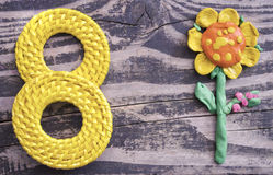 8 March symbol and handmade plasticine flower on wooden background. Happy woman`s day design. Can be used as a decorative greeting Stock Photo