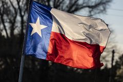 MARCH 6, 2018 - TEXAS STATE FLAG - Texas Lone Star flag stands out against a cloudless blue. Star, background. MARCH 6, 2018 - TEXAS STATE FLAG - Texas Lone Star stock photography