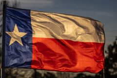 MARCH 6, 2018 - TEXAS STATE FLAG - Texas Lone Star flag stands out against a cloudless blue. Waving, Blue. MARCH 6, 2018 - TEXAS STATE FLAG - Texas Lone Star royalty free stock images