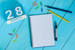 March 28th. Day 28 of month, calendar on blue wooden table background with notepad. Spring time, empty space for text.  Royalty Free Stock Image