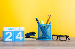 March 24th. Day 24 of month, calendar on light yellow background, workplace with office suplies. Spring time, empty Royalty Free Stock Photography
