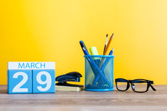 March 29th. Day 29 of month, calendar on light yellow background, workplace with office suplies. Spring time, empty Stock Image
