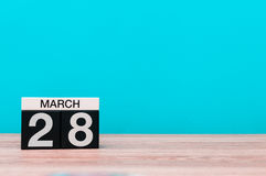 March 28th. Day 28 of month, calendar on table with turquoise background. Spring time, empty space for text Royalty Free Stock Photos