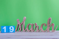 March 19th. Day 19 of month, daily wooden calendar on table and green background. Spring day. Earth Hour and Stock Photos