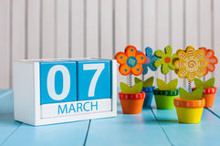 March 7th. Image of march 7 wooden color calendar with flower on white background.  First spring day, empty space for Royalty Free Stock Image