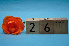 26 March on wooden blocks with an orange rose. On a blue background stock photos