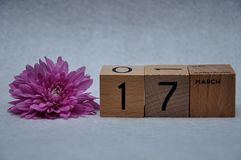 17 March on wooden blocks with a pink daisy. On a white background royalty free stock photography