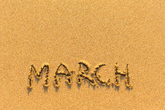 March - word inscription on the gold sand  beach. Royalty Free Stock Images