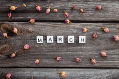 March word is made of bright wood cubes on a dark wooden background Stock Photo