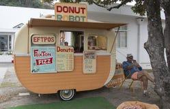 Marchand ambulant de café et de butées toriques parlant par le téléphone Image libre de droits