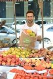 Marchand de légumes vendant les fruits certifiés organiques. Photographie stock libre de droits