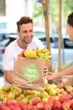 Marchand de légumes vendant les fruits et légumes organiques. Images libres de droits