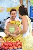 Marchand de légumes vendant les fruits et légumes organiques. Image libre de droits
