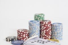 Marchand de tisonnier et pile de jetons de poker sur le blanc Photos libres de droits