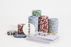 Marchand de tisonnier et pile de jetons de poker sur le blanc Image stock