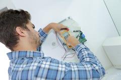 Marchand fixant la question électrique avec le dessiccateur de main photo stock