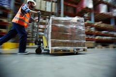 Marchandises au détail mobiles de travailleur dans le grand entrepôt image libre de droits