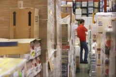 Marchandises emballées en cellophane avec l'homme à l'arrière-plan à l'entrepôt Image libre de droits