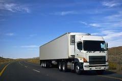Marchandises lourdes en transit par l'intermédiaire des routes goudronnées Photo stock