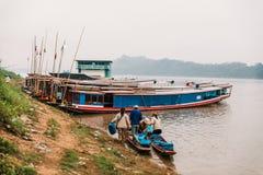 Marchandises mobiles de personnes à la terre en le bateau en rivière chez Luang Prabang, Laos Photographie stock libre de droits