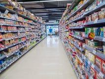 Marchandises sur des étagères de boutique et client dans le supermarché, Bangkok Image stock