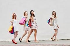 Marchant quatre amies minces de femmes avec des paniers Images stock