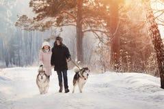 Marche avec le crabot en hiver le couple aimant marche dans la neige photographie stock