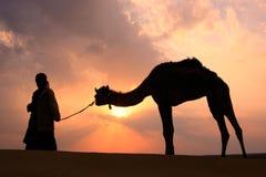 Marche bédouine silhouettée avec son chameau au coucher du soleil, deser de Thar Photographie stock