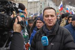 Marche commémorative de Nemtsov Le journaliste étranger avec un microphone rapporte de la scène image libre de droits
