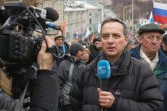 Marche commémorative de Nemtsov Le journaliste étranger avec un microphone rapporte de la scène images stock