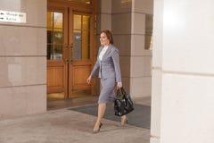 Marche d'une chevelure rouge de femmes d'affaires Image stock